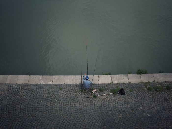On the banks of the Tiber Streetphotography EyeEm Best Shots Urban Fishing Water Sitting Lake High Angle View Nature Day Fishing Men Outdoors Relaxation Lifestyles Real People One Person Tranquility Scenics - Nature