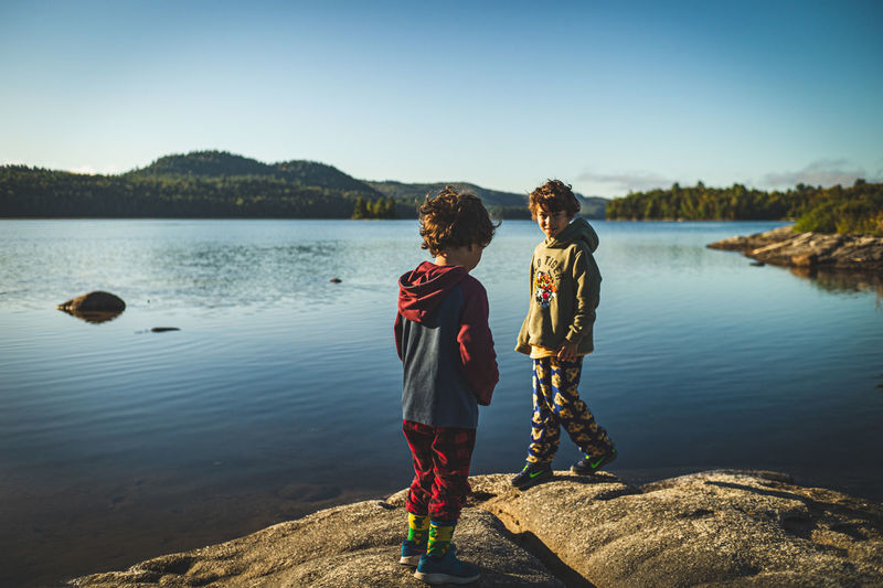Two boys standing by lake against sky