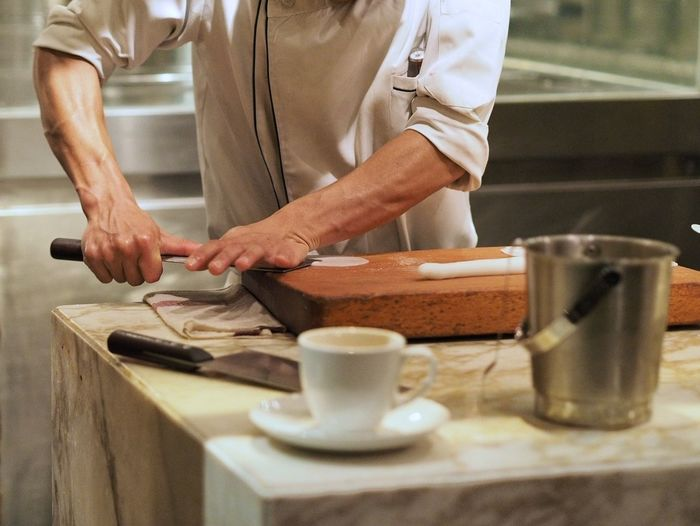 Midsection Of Chef Preparing Food At Commercial Kitchen
