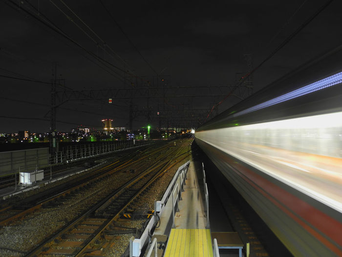 Blurred motion of train on railroad track against sky at night