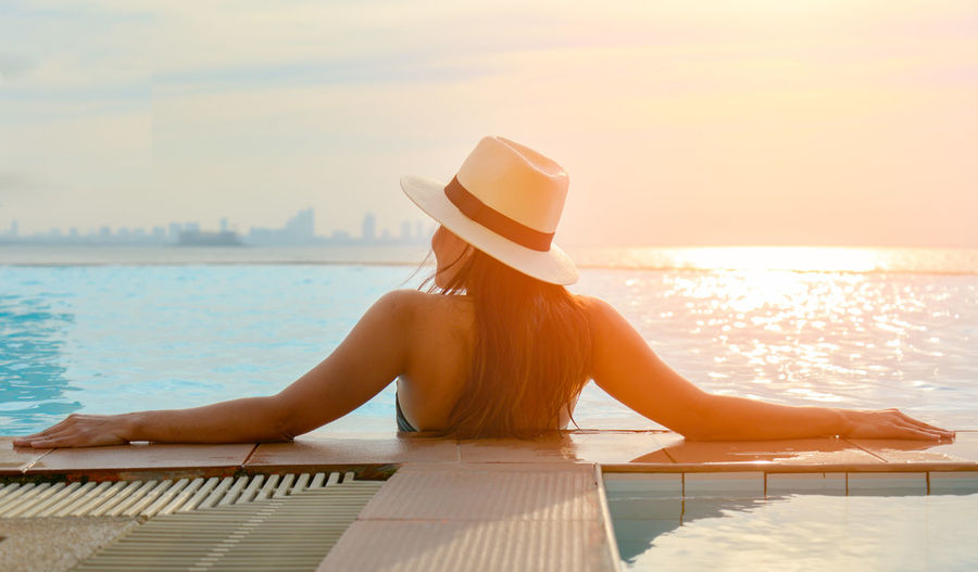 Rear view of woman sitting on swimming pool against sky