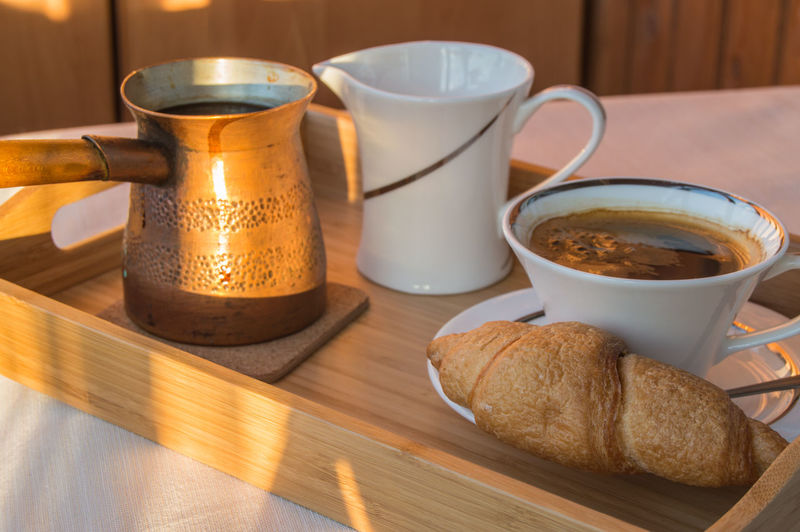 Breakfast is served on a wooden tray with copper pots, a cup of coffee and croissants sunlight