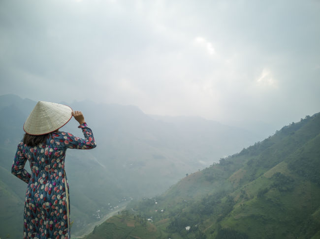 Young Vietnamese women facing and pose for camera with stunning view of the Nho Que river surrounded by mountains from the Ma Pi Leng pass in northern Vietnam Mountain Cloudy Green Color Meo Vac Vietnam Vietnamese Ao Dai Beauty In Nature Clothing Cloud - Sky Day Environment Fog Hat Landscape Leisure Activity Looking At View Mountain Mountain Range Nature Non-urban Scene One Person Outdoors People Pose Real People Scenics - Nature Sky Standing Sunrise Traditional Dress Tranquil Scene Tranquility Valley Women