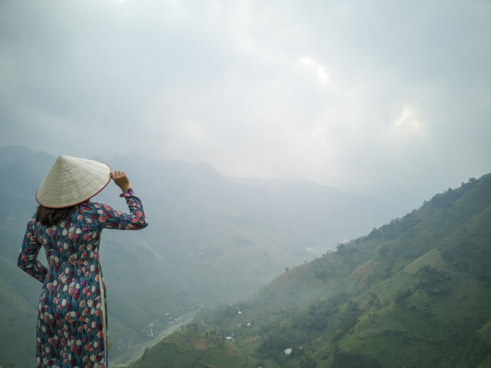 Rear View Of Woman Wearing Asian Style Conical Hat Standing Against Mountains In Foggy Weather