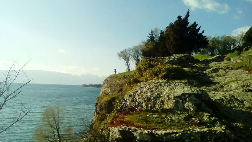 Here Belongs To Me Lake View Ohridlake Macedonia Ohrid Water Blue Sky Silhouette Person Hill Trees Rocks Grass Nature Perfect Mountain Taking Photos Relaxing The KIOMI Collection