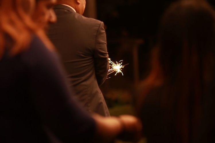 Man holding lit sparkler against sky at night