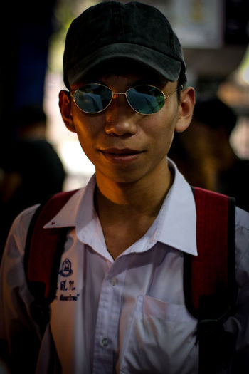 Portrait of young man wearing sunglasses at night