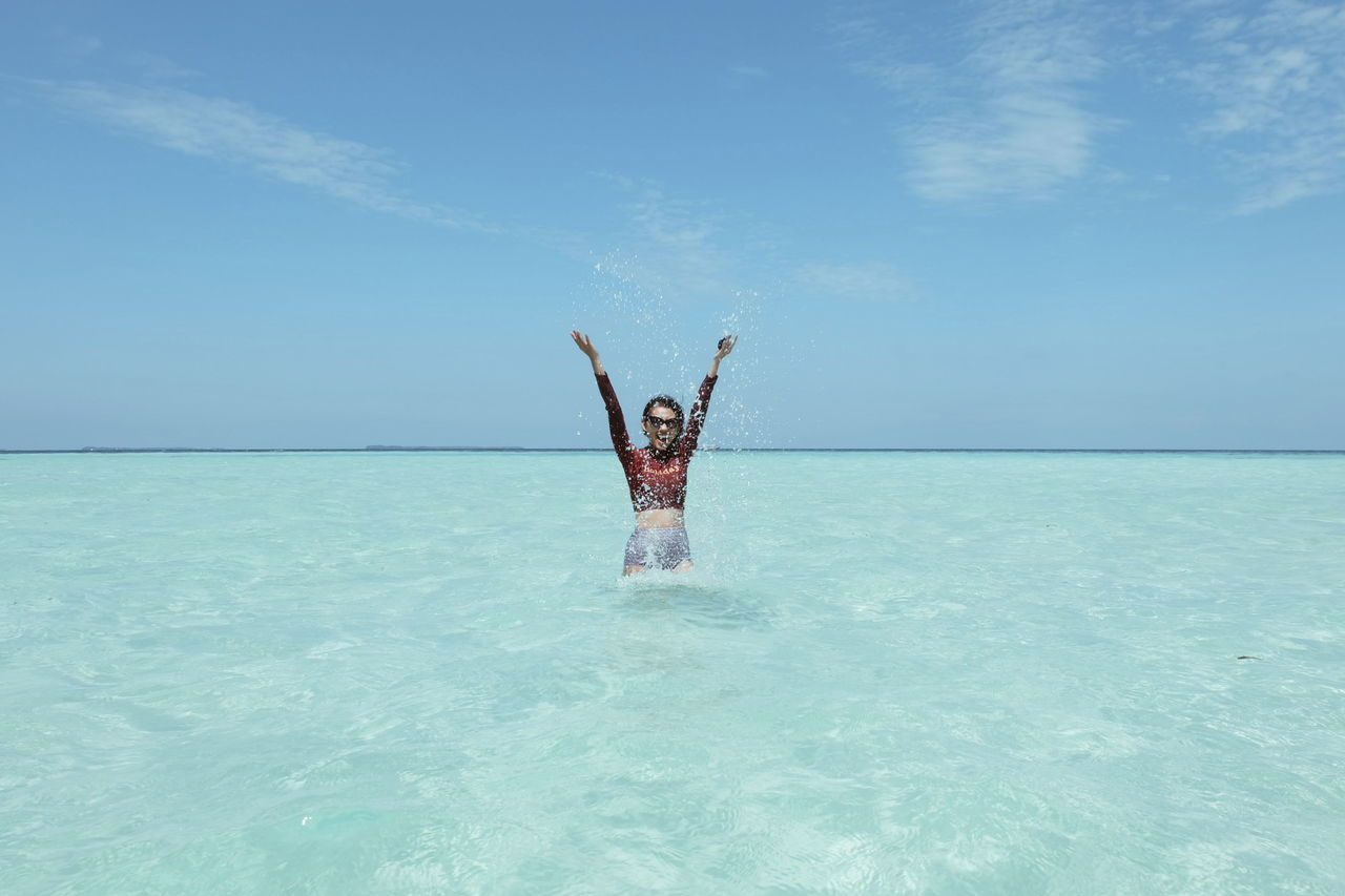 Woman With Arms Raised Standing In Sea Against Sky