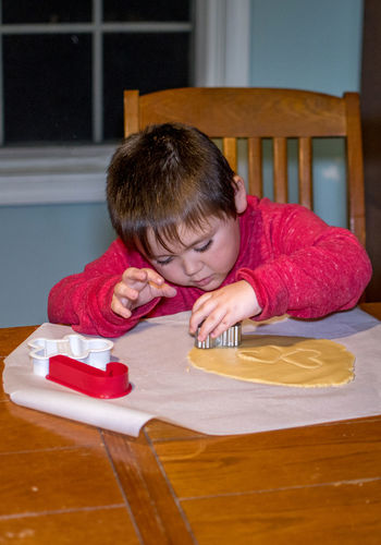 A little boy uses cookie cutters to stamp shapes into sugar cookie dough Childhood Child One Person Table Portrait Indoors  Front View Boys Innocence Lifestyles Cookies Cookie Dough Biscuits Baking Cookies Cookie Cutters Males  Red Young Adult Kid Kitchen Table Indoors  Home Happy Creative Raw Ingredients