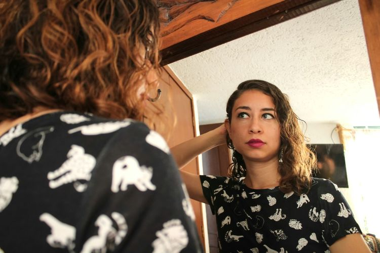 Low Angle View Of Young Woman Reflecting In Mirror At Home
