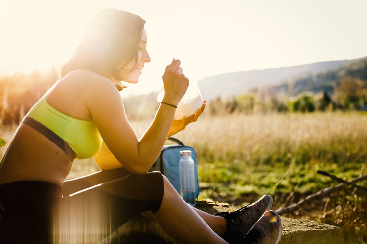 Young sporty woman eating healthy lunch in the field at the sunset Sporty Woman Sporty Girl Young Woman Crop Top Sportswear Field Runner Yoga Healty Fitness Attractive Sunset Sport Clothes Spring Summer Brunette Leggings Crop Tank Outdoors Lifestyles Exercising Recreational Pursuit Energy Nature Caucasian Athlete Sitting Real People One Person Three Quarter Length Leisure Activity Sunlight Young Adult Side View Young Women Land Casual Clothing Focus On Foreground Day Beautiful Woman Hairstyle Lens Flare