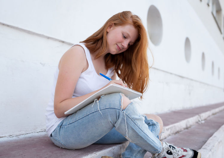 Young woman smiling while sitting outdoors