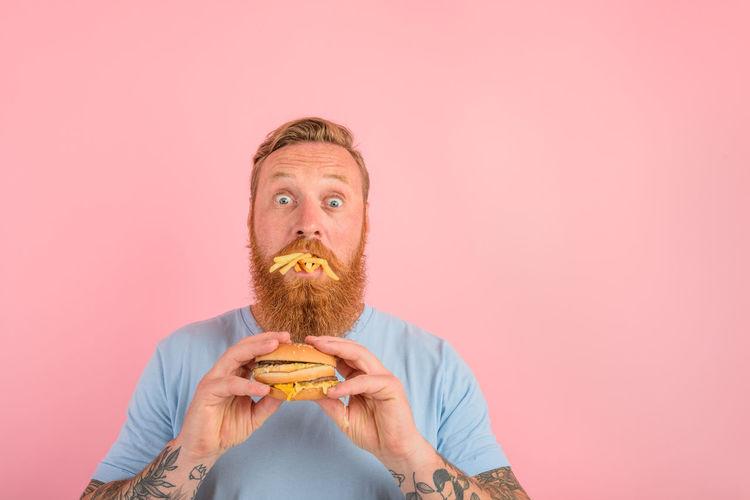 Portrait of man holding ice cream against orange background