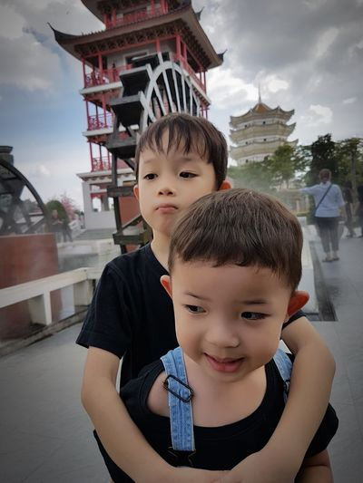 Cute Brothers Looking Away While Standing In City