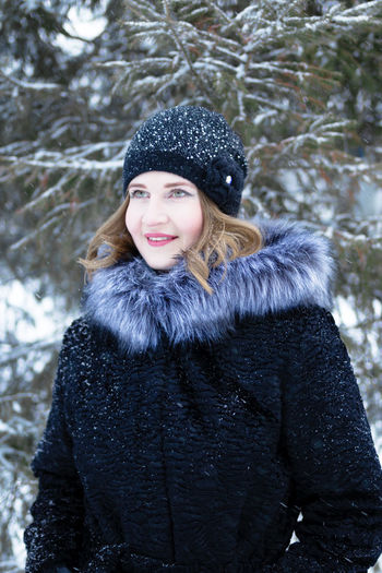 Young woman smiling in snow during winter