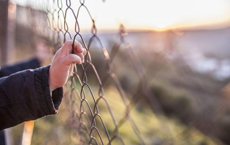 Midsection of man holding cigarette against fence