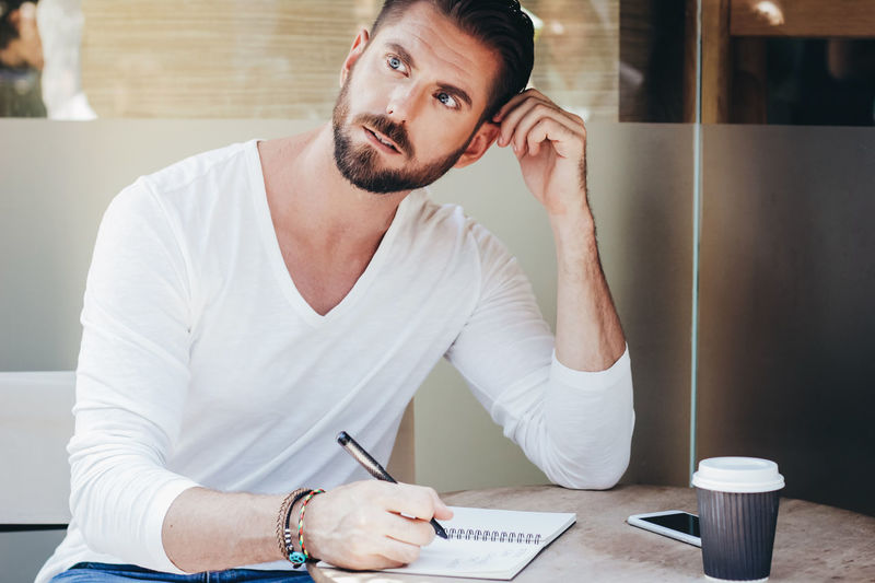 Smart businessman thinking while writing on notebook at sidewalk cafe Adult Beard Cafe Day Hand Handsome Hipstergirl Lifestyles Man Not One Man Only One Person Outdoors People Portrait Sitting Smart Smartphone Startup Take Away Thinking Working Writing