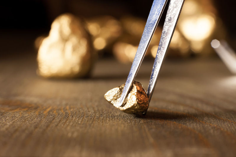 checking golden nuggets with tweezers Golden Industry New Nuggets Precious Shiny Sparkle Treasure Abundance Arranged Capital Close-up Displayed Expensive Financing Fortune Geology Huge Many Metal Stone Surface Table Wealth Wood - Material