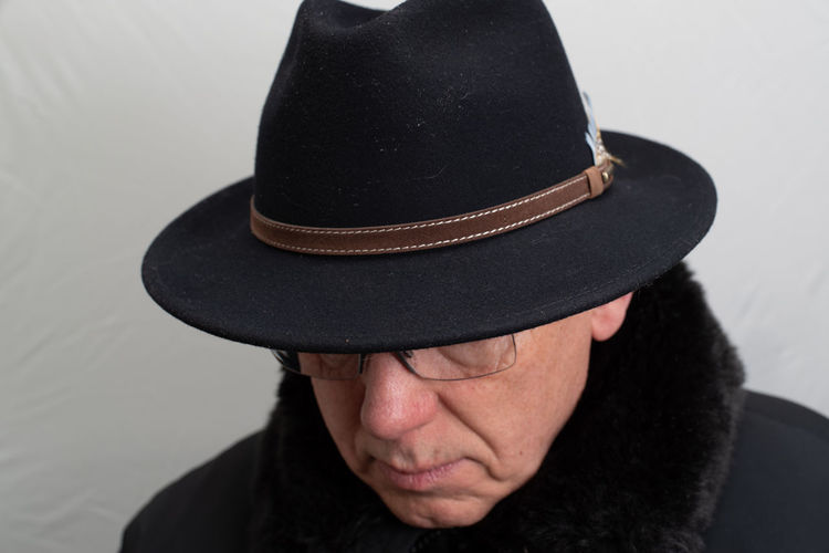 Close-up of man wearing hat against wall