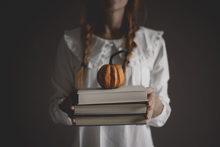 Midsection of woman reading book against black background