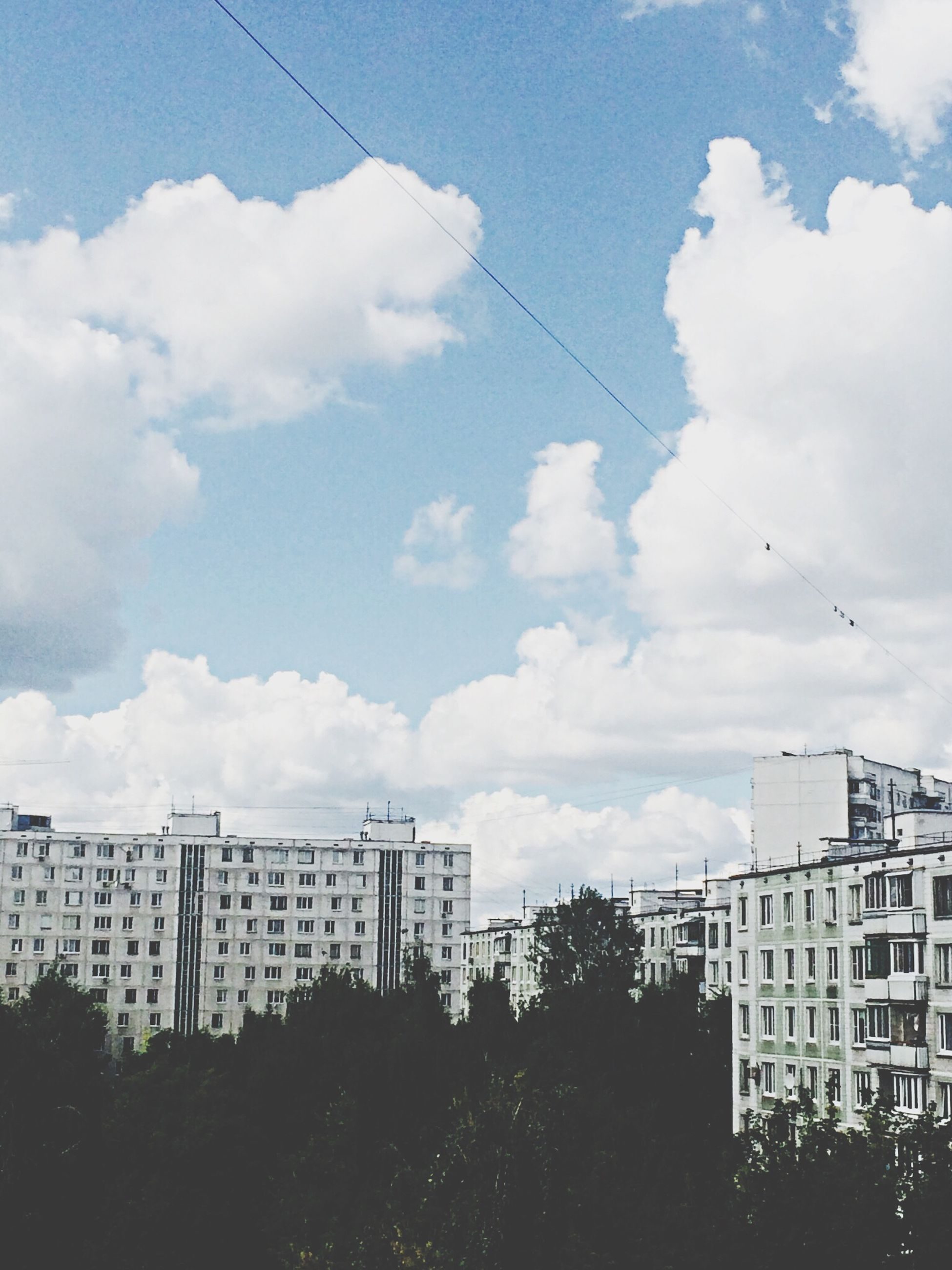 sky, architecture, building exterior, built structure, cloud - sky, low angle view, cloudy, cloud, building, city, day, outdoors, residential building, no people, tree, residential structure, house, nature, bird, overcast