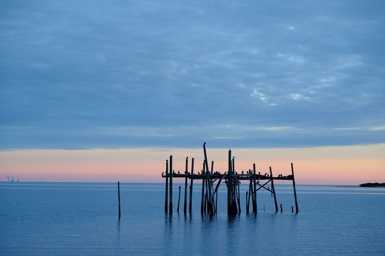 Wooden posts in sea against cloudy sky at sunset