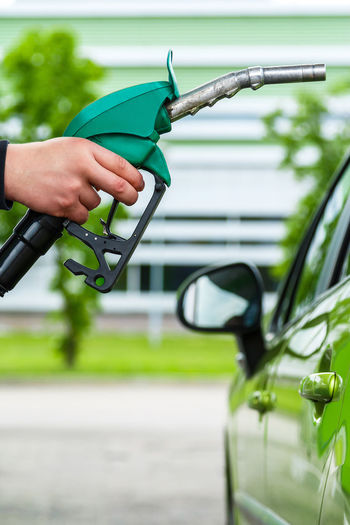 Cropped hand of man filling gasoline in car