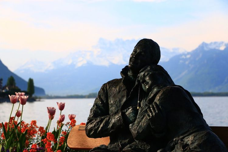 Human statues on bench at lakeshore against mountains