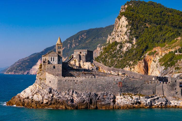 Historic buildings by sea against blue sky