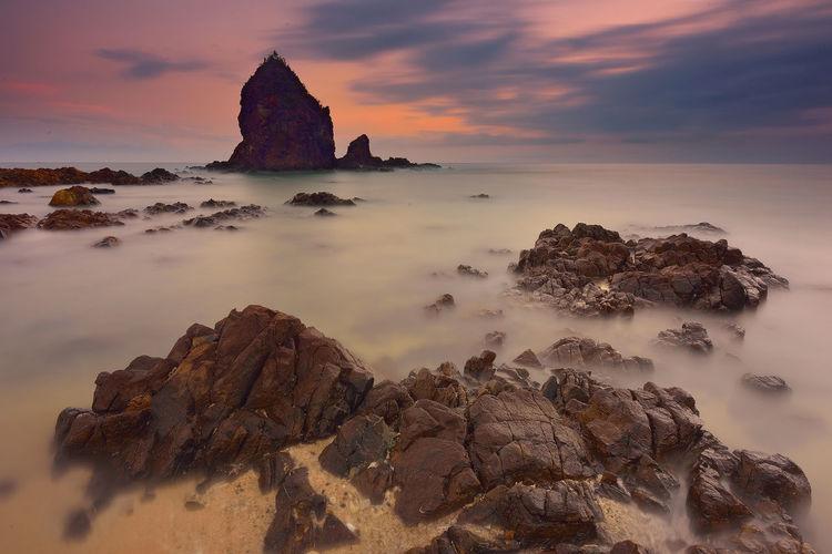 Water Sea And Sky Sea Stack Sunrise Nature Sea Weather Orange Color Dusk Rock Formation Seascape Rock - Object Sand Beach Orange Shore Cloud