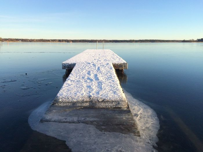 Snow On Damaged Jetty In Lake Against Sky