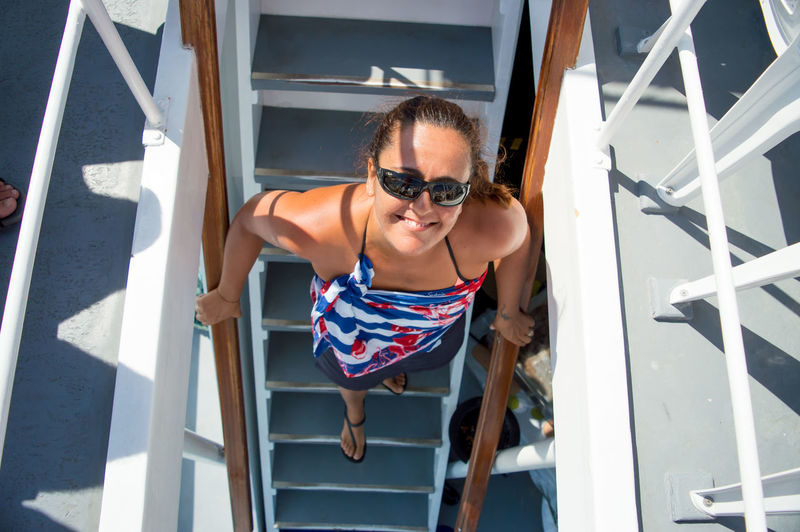 High Angle View Of Smiling Woman Standing On Steps In Cruise