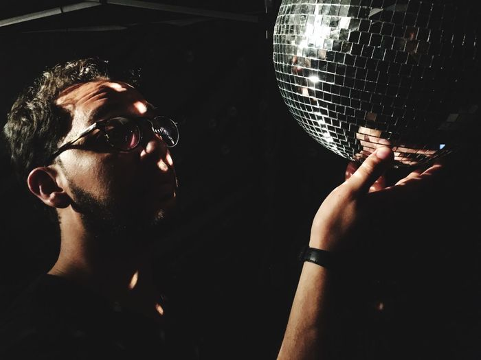 Man touching disco ball in dark