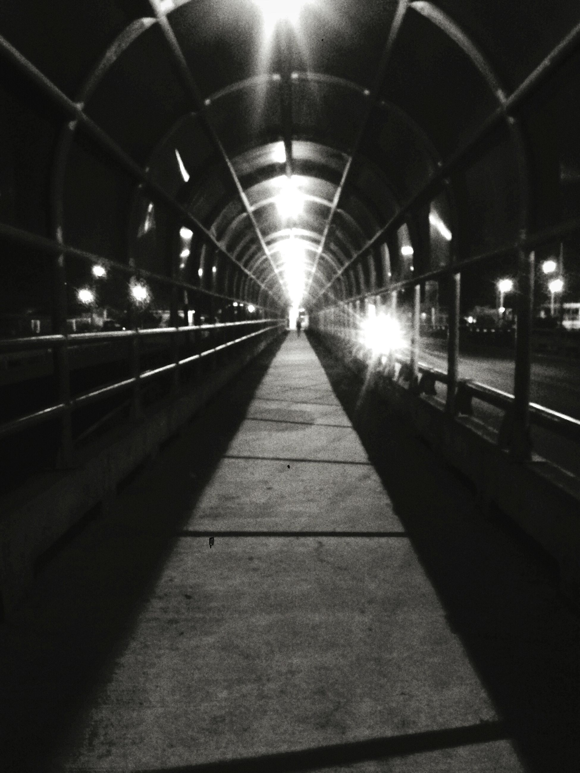 the way forward, illuminated, diminishing perspective, transportation, night, vanishing point, built structure, architecture, indoors, lighting equipment, empty, incidental people, surface level, tunnel, walkway, city, long, no people, railing, railroad track