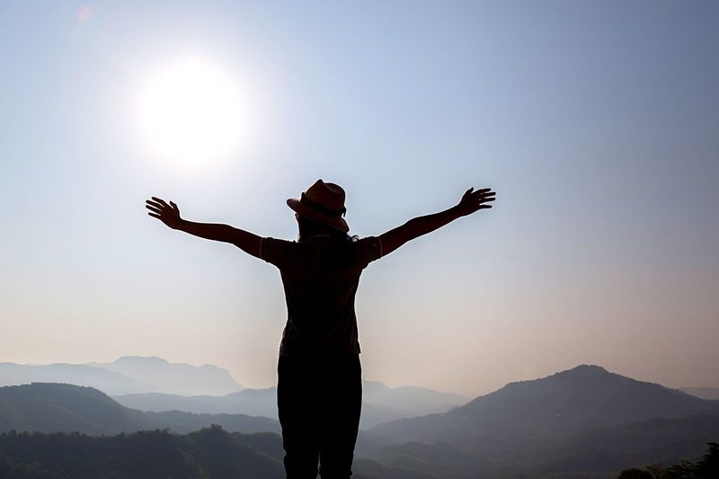 Low angle view of silhouette person standing on mountain against sky