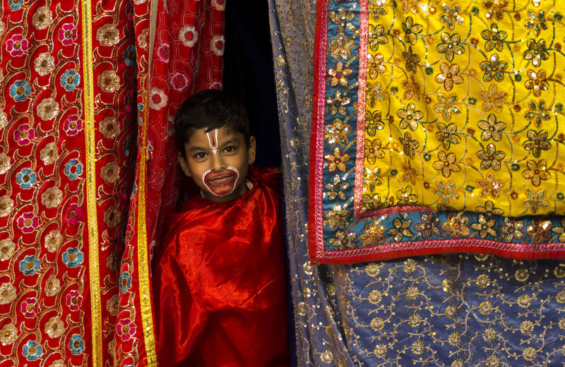 Portrait of cute boy with face paint standing amidst colorful curtains