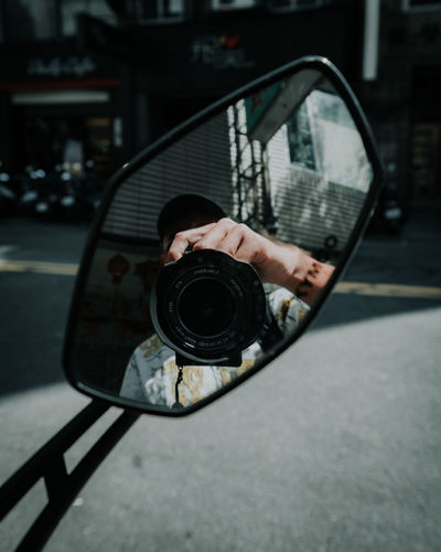 Reflection of man photographing with camera on side-view mirror of motorcycle
