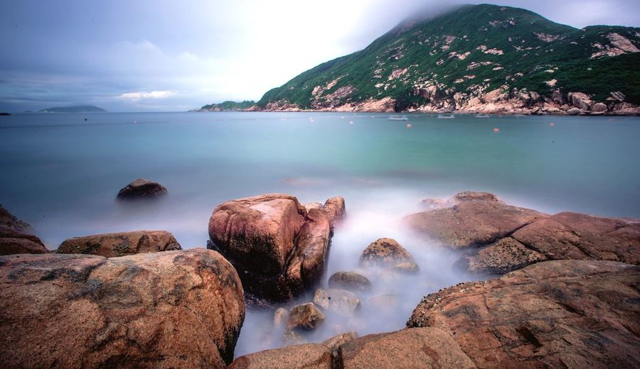Scenic view of sea against mountain seen from rocky shore at shek o