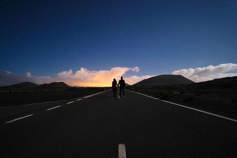 People standing on road against sky