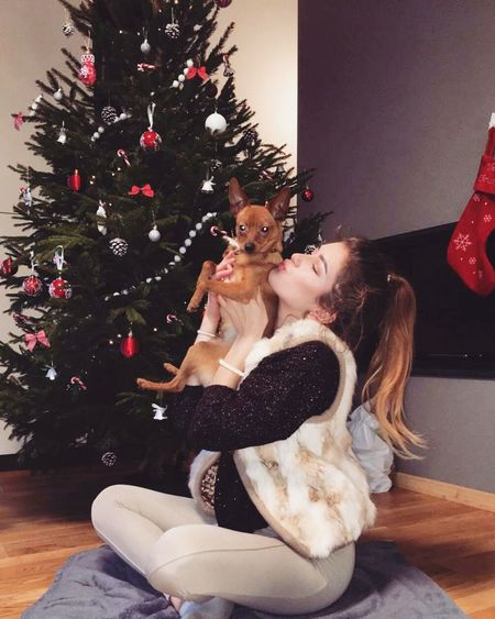 Young woman with dog sitting on tree at home