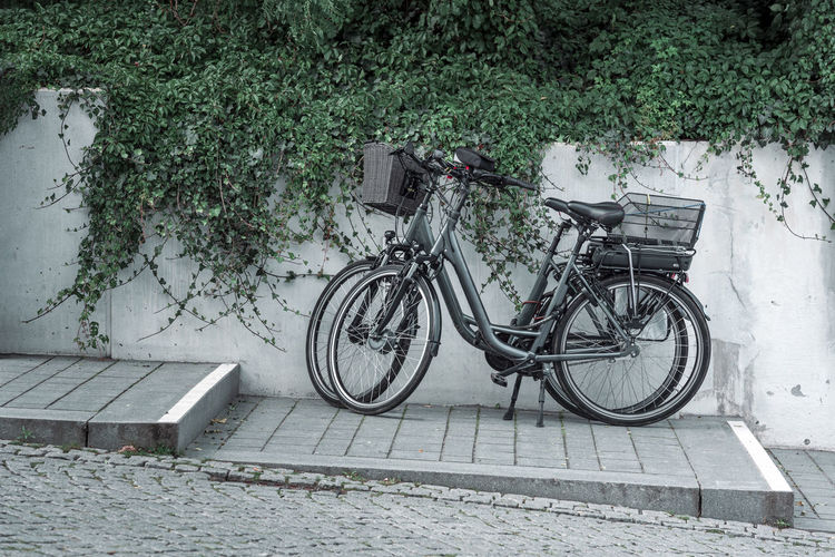 Bicycle parked on sidewalk by wall
