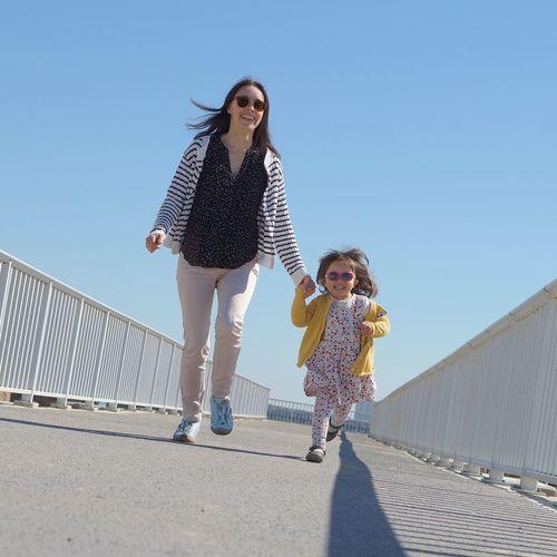 Happy girl walking on walkway against clear sky