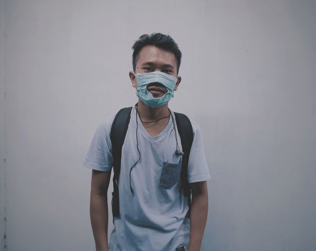 Portrait of young man wearing torn mask against wall