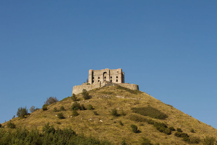 Low angle view of fort against clear blue sky