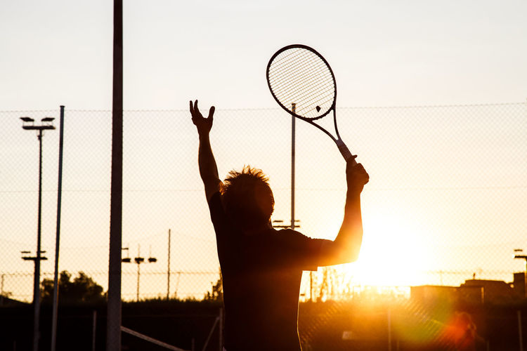 Rear view of silhouette young man playing tennis at court