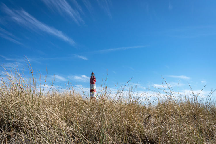 Man standing by lighthouse on land against sky