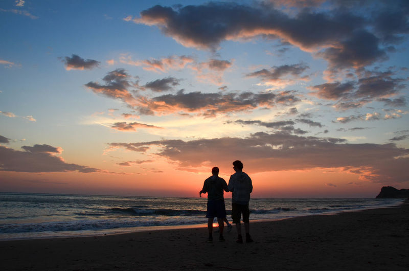 Silhouette friends standing on beach against sky during sunset