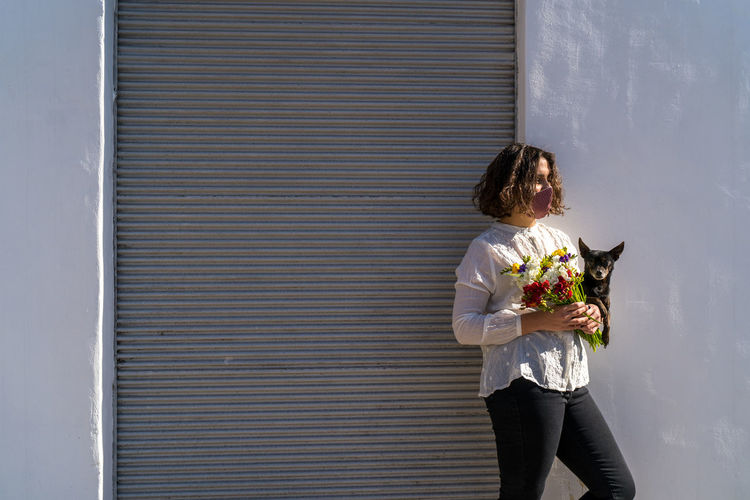Young woman with mask holding bouquet of colorful flowers with her dog, white wall background