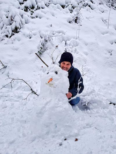 Man Making Snowman During Winter