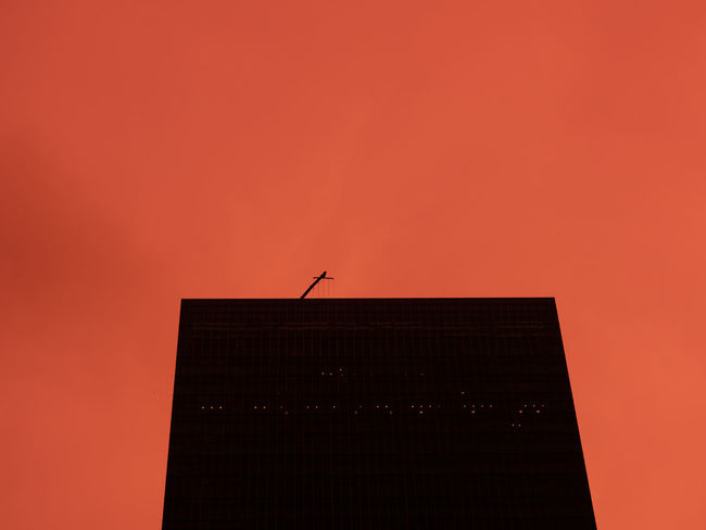Dark office tower with several light on, under sky in dramatic color Architecture Sky Building Exterior Low Angle View Silhouette Copy Space Orange Color Abstract Abstract Photography Silhouette Crane Roof Rooftop Office Building Office Towers Dark Black Red Red Sky Overtime Work Overtime!! @office Dramatic Sky Dramatic Color Evening Night